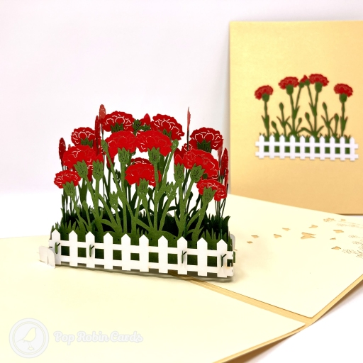 This beautiful floral greetings card is suitable for many occasions with its 3D pop up design showing a patch of vivid red carnation flowers surrounded by a pretty white picket fence. The cover has a flat layered design showing the same scene.