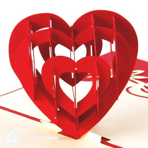 "This romantic greetings card opens to reveal a 3D pop-up heart design, with a stenciled ""I love you"" message to one side. The card is available in vivid red or pink colours."