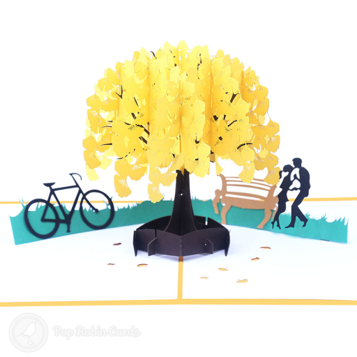 This beautiful card opens to reveal a 3D pop up design showing a romantic scene in an autumnal park, with the silhouette of a couple beneath a tree and a bike nearby. The cover has a stencil design showing the same scene.