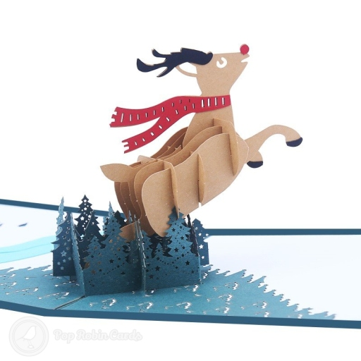 This charming Christmas card opens to reveal a 3D pop-up scene showing Rudolf the Red-nosed Reindeer leaping from a snowy forest, with a red scarf trailing behind him. The cover has a stenciled design also showing Rudolf.