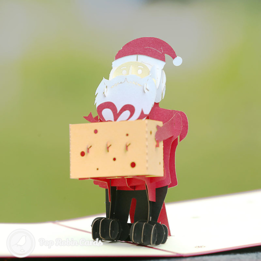 """This funny Christmas card opens to reveal a 3D pop up design showing Santa holding a big Christmas present in a box. The cover has a stencil design with a """"Merry Christmas"""" message."""