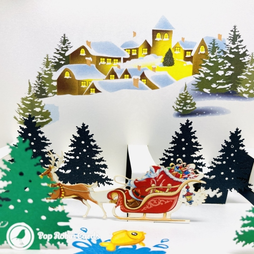 This charming Christmas card opens to reveal a 3D pop up design showing a town at Christmas, with Santa passing on his sleigh in a snowy forest nearby.