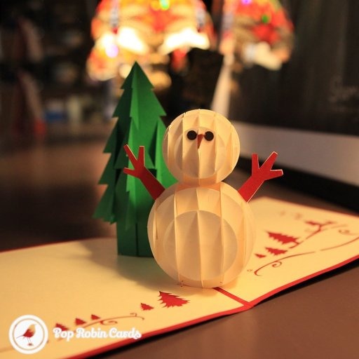 Inside this Christmas card are a 3D pop-out snow man and a green pine tree. The outside shows a stencilled snowflake, snow man and Christmas tree.