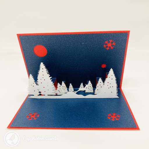 "This special and atmospheric Christmas card has a 3D pop up design showing a snowy nighttime forest scene, with a reindeer leaping through trees. The cover has a stencil design showing reindeer, a Christmas tree and a ""Merry Christmas"" message."
