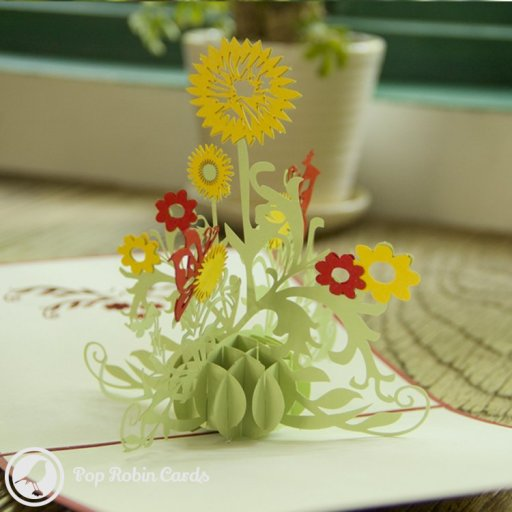 This beautiful card opens to reveal a tasteful 3D pop-up design showing a tall sunflower with green leaves and other flowers around it. The cover has a stencil design showing sunflowers and butterflies. The card is sure to delight anyone who loves flowers and nature.
