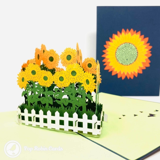 This beautiful greetings card is perfect for many occasions with its 3D pop up design showing a cheerful patch of bright yellow sunflowers with green stems and leaves in a pretty white picket fence. The cover has shows a bright yellow and orange sunflower.