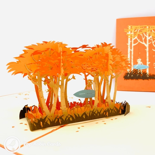 This gorgeous and atmospheric greetings card has a 3D pop up design showing a surfer walking among a grove of palm trees lit up in orange by a sunset from the sea.