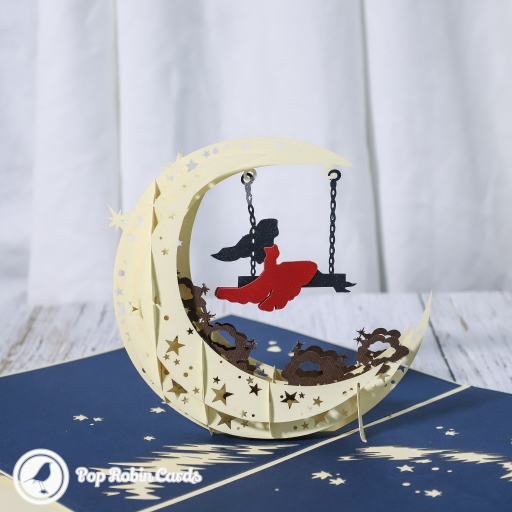 This amazing card opens to reveal a beautiful 3D pop up design showing a silhouetted figure on a swing inside a crescent moon. The cover also has a crescent moon design.
