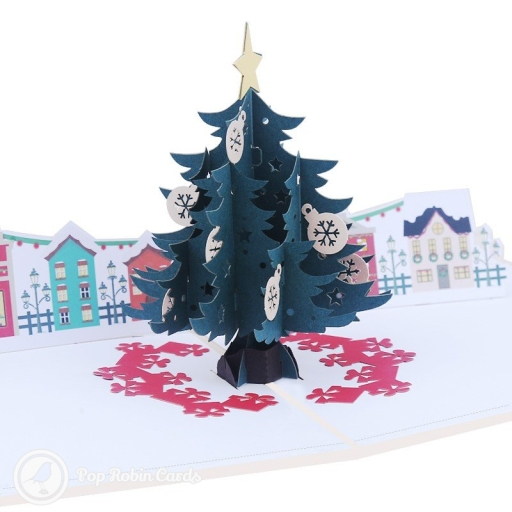"This stylish Christmas card opens to reveal a 3D pop-up scene showing a tall, decorated Christmas tree in a town square surrounded by brightly coloured townhouses. The cover shows a snowy fence post with a ""Merry Christmas"" message."