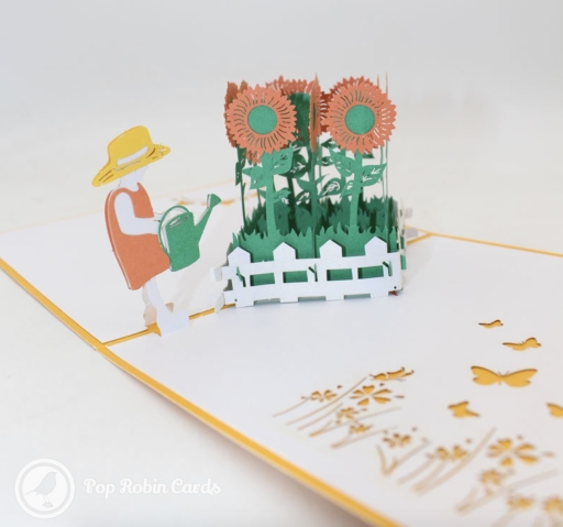 This greetings card has a 3D pop up design showing a figure with a sun hat watering a patch of tall sunflowers with a watering can. The cover design also shows a sunflower.