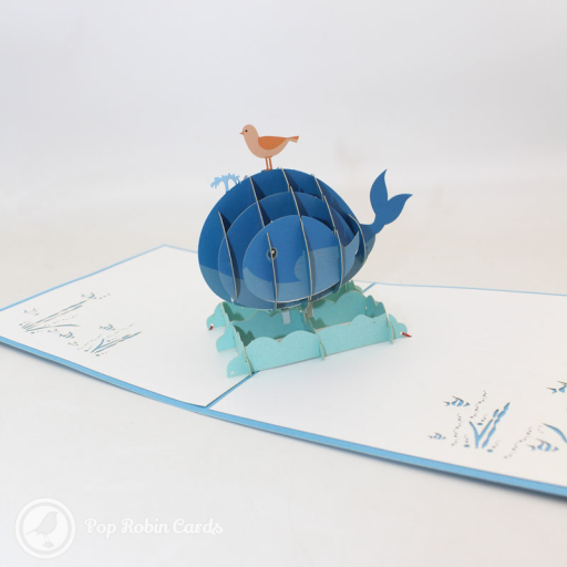 This charming card opens to reveal a 3D pop up design showing a small bird riding on top of a whale cresting waves at sea. The cover has a stencil design showing the same pair.